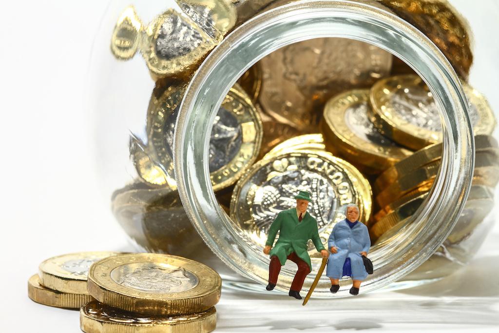 Conceptual diorama image of elderly miniature figures sat on